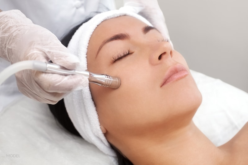 Woman undergoing a microdermabrasion treatment with her cosmetic provider.