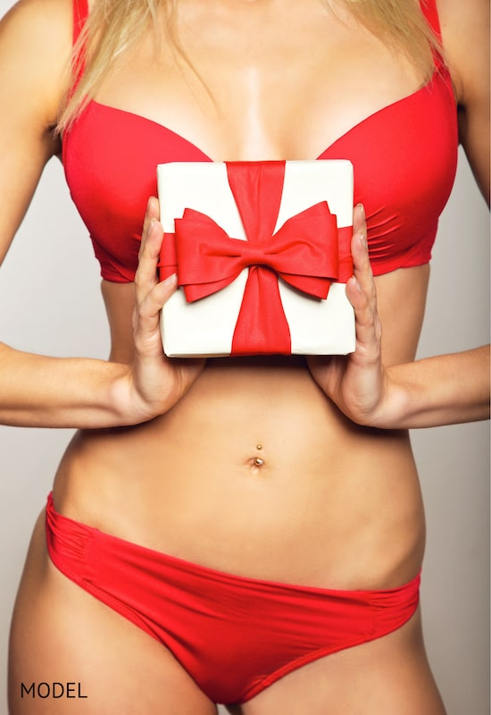 Woman in red underwear holding a gift in front of her breasts